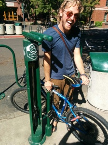 """I loved this clever """"bike repair station"""" bolted into the ground on the U of O campus. Wrenches and screws hang down inside, protected, and there is a pump on the outside. Brilliant! This guy was pumped to be in my photo."""